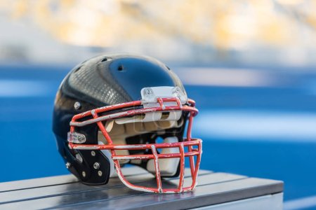 close-up shot of american football helmet lying on bench
