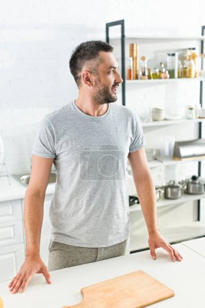 side view of adult man standing near table with cutting board on kitchen