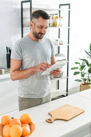 happy man using digital tablet near table on kitchen