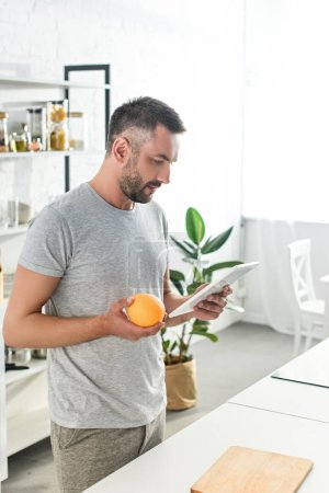 side view of man holding orange and looking for recipe in digital tablet on kitchen