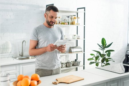 Photo for Adult smiling man with digital tablet looking for recipe near table on kitchen - Royalty Free Image