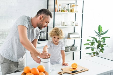 father and little son making fresh orange juice by squeezer on table at kitchen son