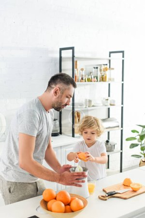 Photo for Little boy putting orange in squeezer for making fresh juice while father helping him at kitchen - Royalty Free Image