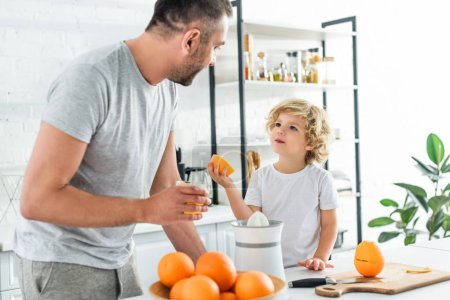 Photo for Son and father looking at each other after making fresh orange juice at kithen - Royalty Free Image