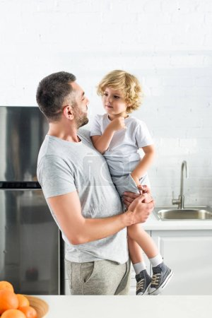 side view of father talking to son and holding him hands at kitchen