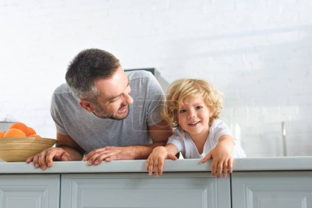 Photo for Happy father and son having fun and laying on tabletop at kitchen - Royalty Free Image