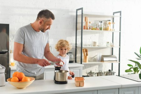 side view of man breaking egg by knife for making dough while his son standing near at kitchen