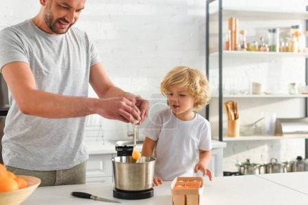 Photo for Adorable boy looking how his father breaking egg into bowl at kitchen - Royalty Free Image