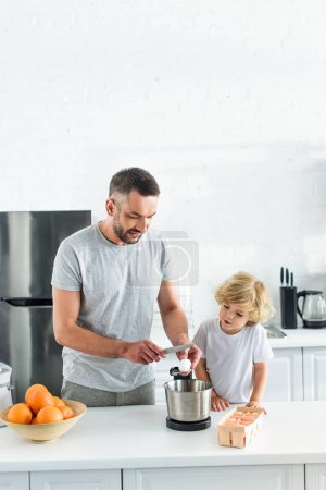 Photo for Man with son breaking egg by knife into bowl at kitchen - Royalty Free Image