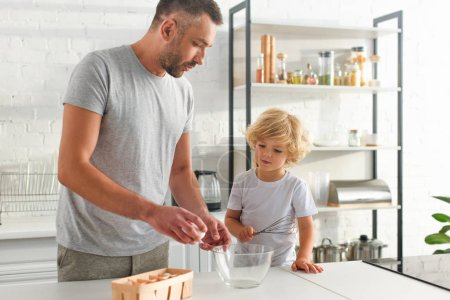 father with egg and son with whisk preparing to make dough at kitchen