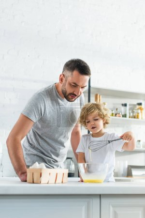 Photo for Father with son whisking eggs in bowl at kitchen - Royalty Free Image