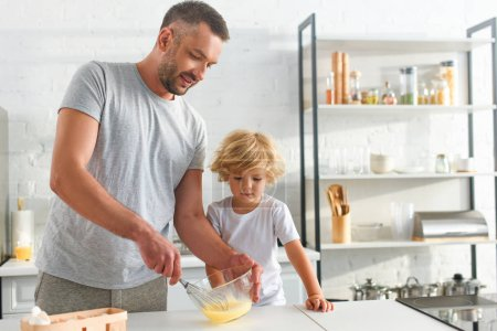 smiling father whisking eggs in bowl while his son standing near at kitchen