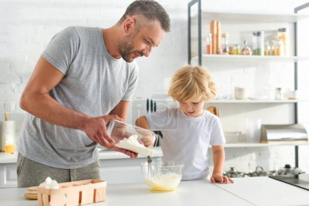 Photo for Man pouring flour into bowl while his son whisking eggs at kitchen - Royalty Free Image