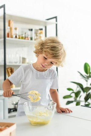 Photo for Adorable little boy making dough by whisk on kitchen - Royalty Free Image