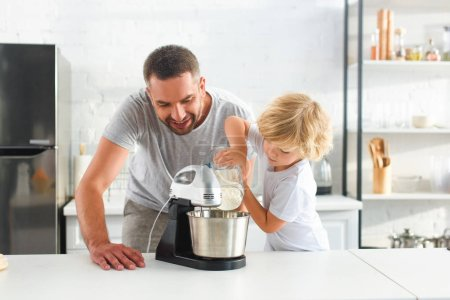 little boy pouring flour into mixer bowl while his father standing near at kitchen