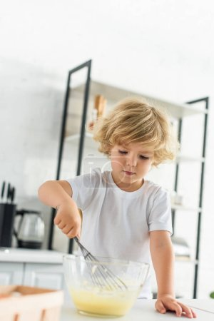 concentrated little boy making dough by whisk on table at kitchen