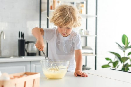 Photo for Little boy making dough by whisk on table at kitchen - Royalty Free Image