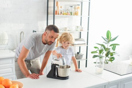 Photo for Father watching how his son using mixer for making dough at kitchen - Royalty Free Image
