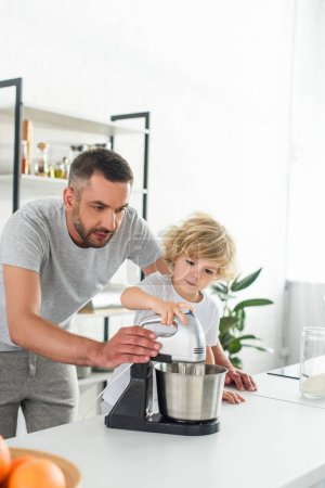 focused man helping his son using mixer for making dough at kitchen