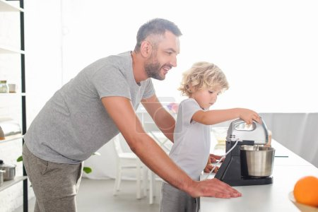 side view of smiling man standing near son while he using mixer for making dough at kitchen