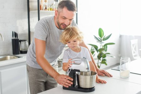 Photo for Smiling man helping his son using mixer for making dough at kitchen - Royalty Free Image