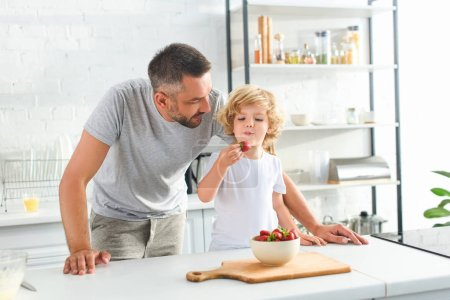father standing near son while he eating strawberry at kitchen
