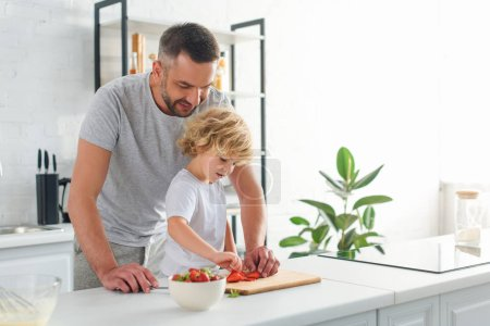man standing with son while he taking strawberry from cutting board at kitchen