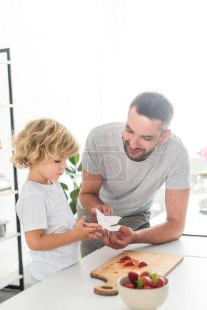 father helping son to wiping hands by napkin near tabletop with strawberries at kitchen