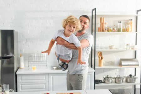 Photo for Father raising up smiling little son at kitchen - Royalty Free Image