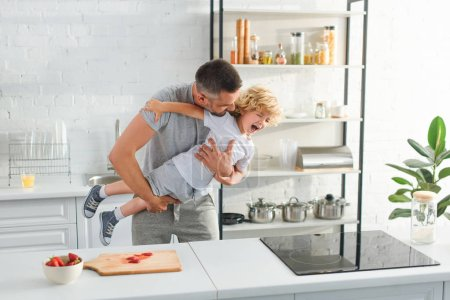 father holding laughing son and tickling him at kitchen