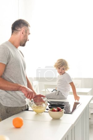 side view of father whisking dough in bowl and talking to son while he sitting on tabletop at kitchen