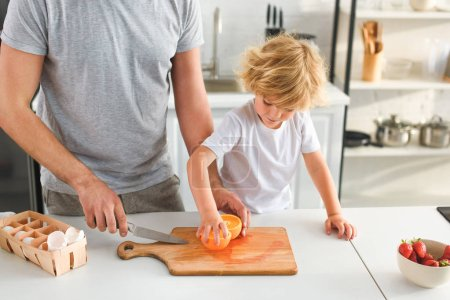 cropped image of man with knife and his son taking of piece of orange from cutting board at kitchen