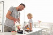 smiling man pouring dough into frying pan while his son sitting near on tabletop at kitchen