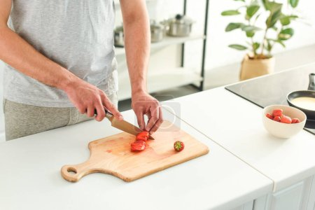 cropped image of man cutting strawberry by knife on table at kitchen