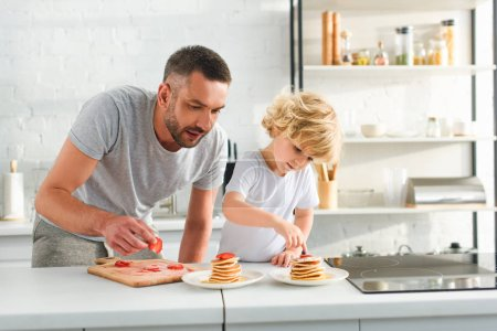 focused little boy with father putting strawberry pieces on pancakes at kitchen