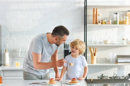 Photo for Smiling father feeding little son by pancakes at kitchen - Royalty Free Image