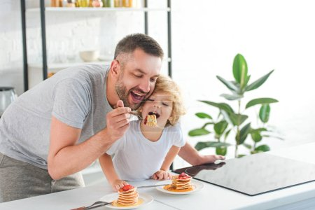 Photo for Smiling father and son eating pancakes near tabletop at kitchen - Royalty Free Image