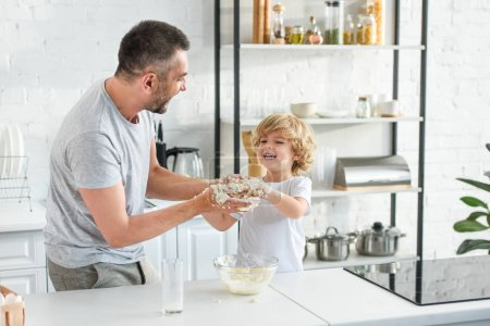 Photo for Happy father and son having fun while making dough in bowl at kitchen - Royalty Free Image