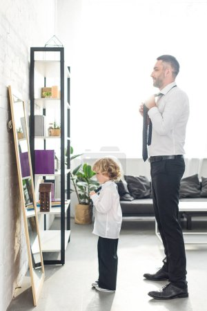 side view of father and son tying neckties over white shirts in front of mirror at home
