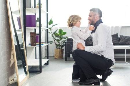 side view of little boy helping father tying necktie at home