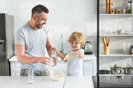 laughing father and son having fun while making dough in bowl at kitchen
