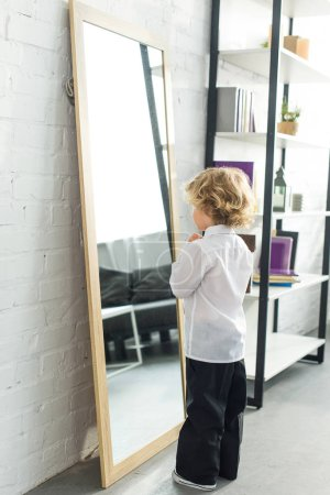 rear view of little boy tying necktie over white shirt in front of mirror at home