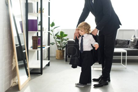 cropped image of man in suit helping son to putting on jacket at home