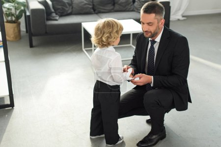 adult man in suit fastening buttons on shirt sleeve of son