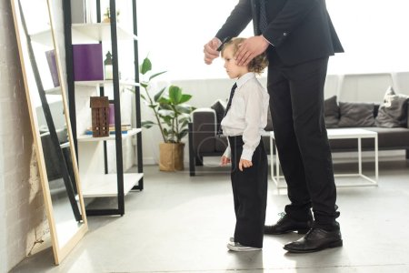 cropped image of father in suit combing son hair in front of mirror at home