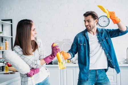 boyfriend and girlfriend having fun during cleaning kitchen and fighting with cleaning tools
