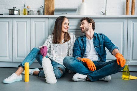 happy couple sitting on floor and looking at each other after cleaning in kitchen