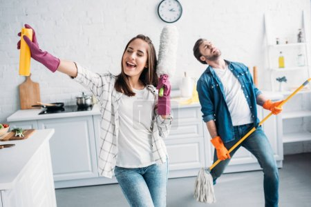 girlfriend and boyfriend in rubber gloves singing and playing mop like guitar in kitchen
