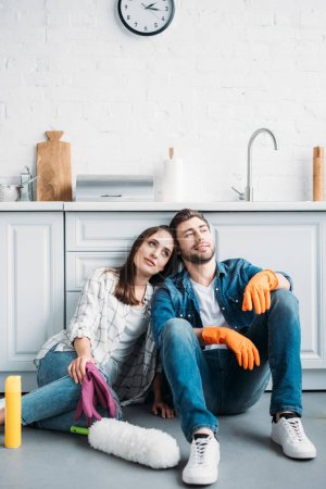 couple sitting on floor and leaning on kitchen counter after cleaning in kitchen