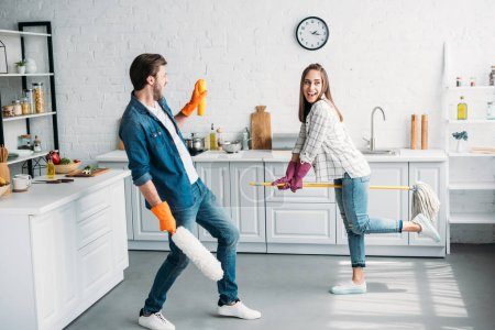 couple in rubber gloves having fun with mop in kitchen